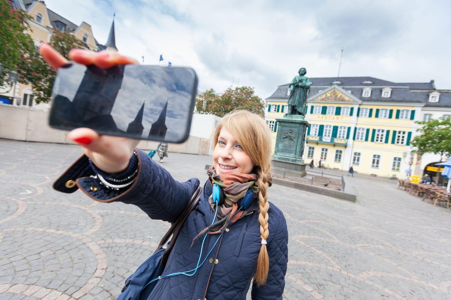 Meisje maakt een selfie voor het beeld van Van Beethoven in Bonn