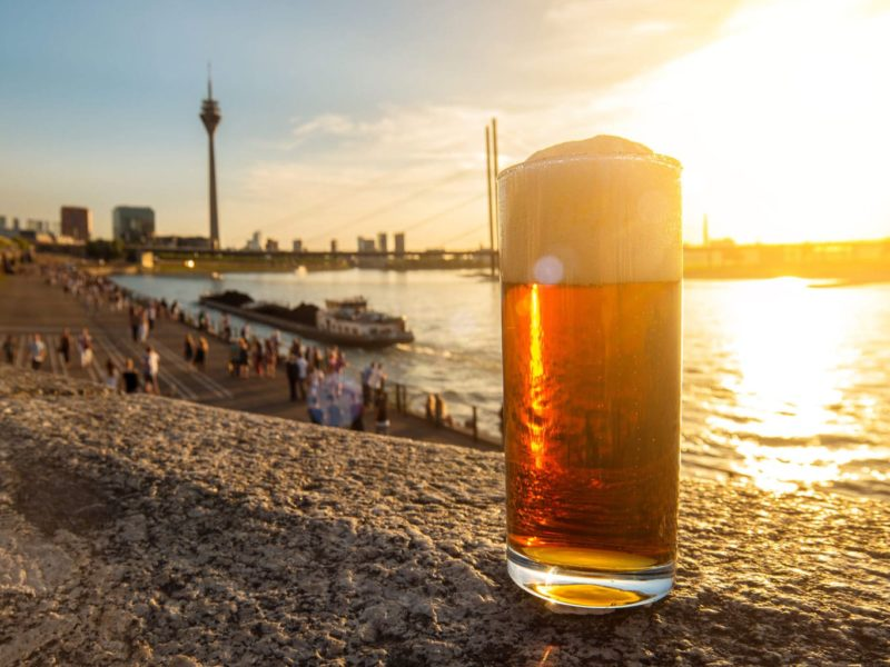 Een glas Altbier met uitzicht op de rijn in Düsseldorf tijdens de zonsondergang