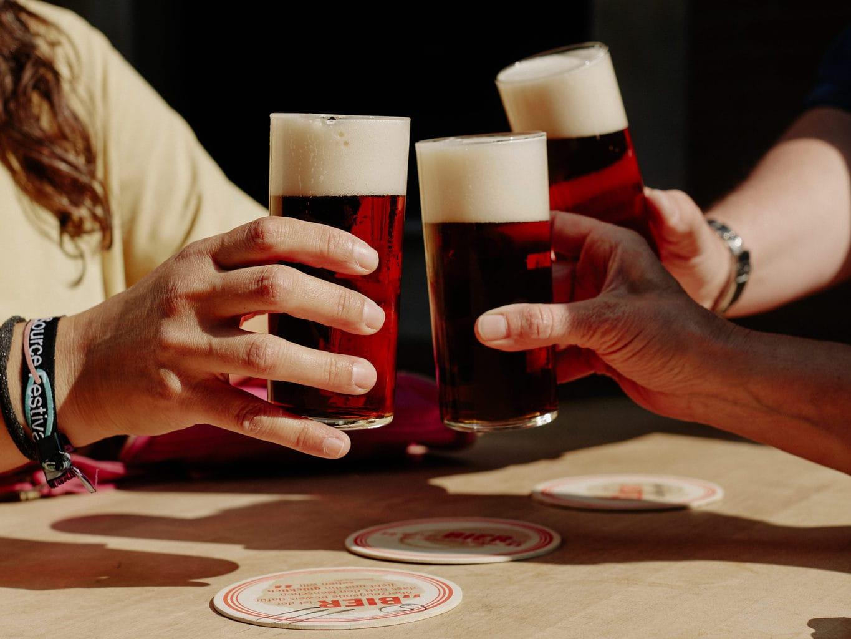 Drie mensen proosten met een glas Altbier in Düsseldorf