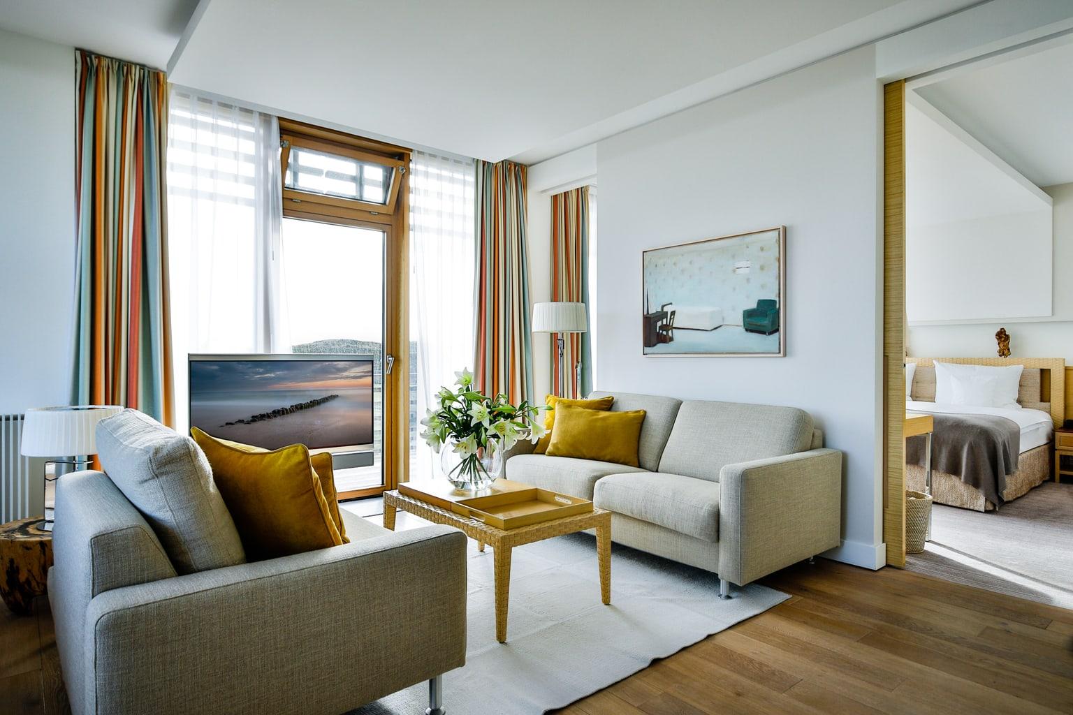 Een suite in het Budersand Hotel op het eiland Sylt met couch en televisie