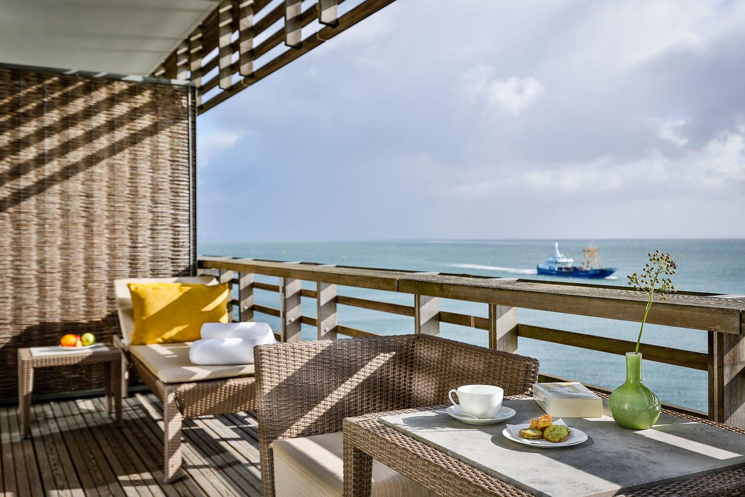 Balkon van een suite in het Budersand Hotel op Sylt met uitzicht op schepen