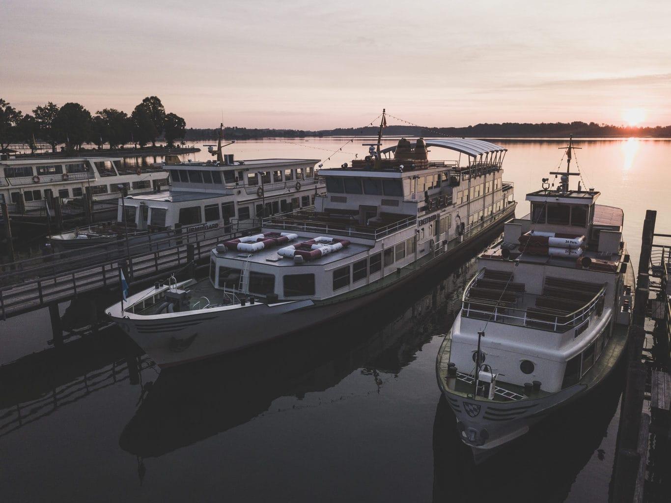 De vloot van Chiemsee Schifffahrt op het meertje tijdens de zonsondergang