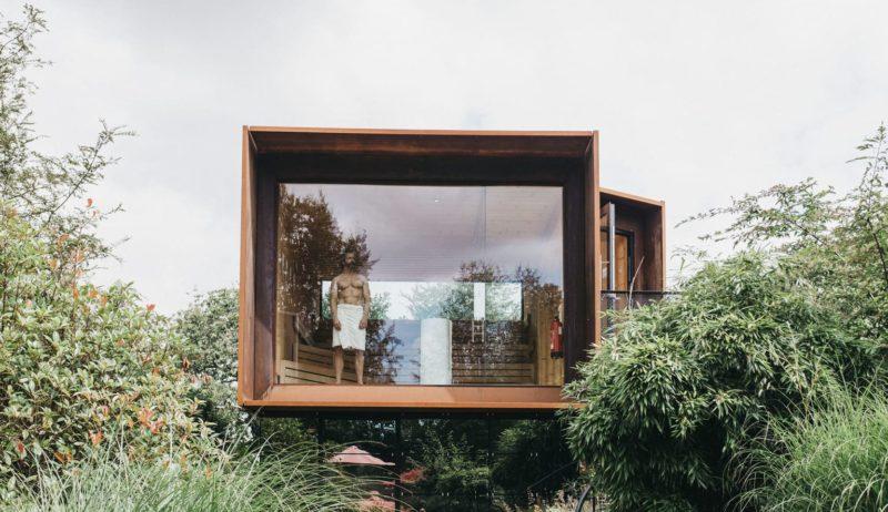 Een man staat aan een raam van een suite in Landgut Voshövel, een van de leuke designhotels in Duitsland