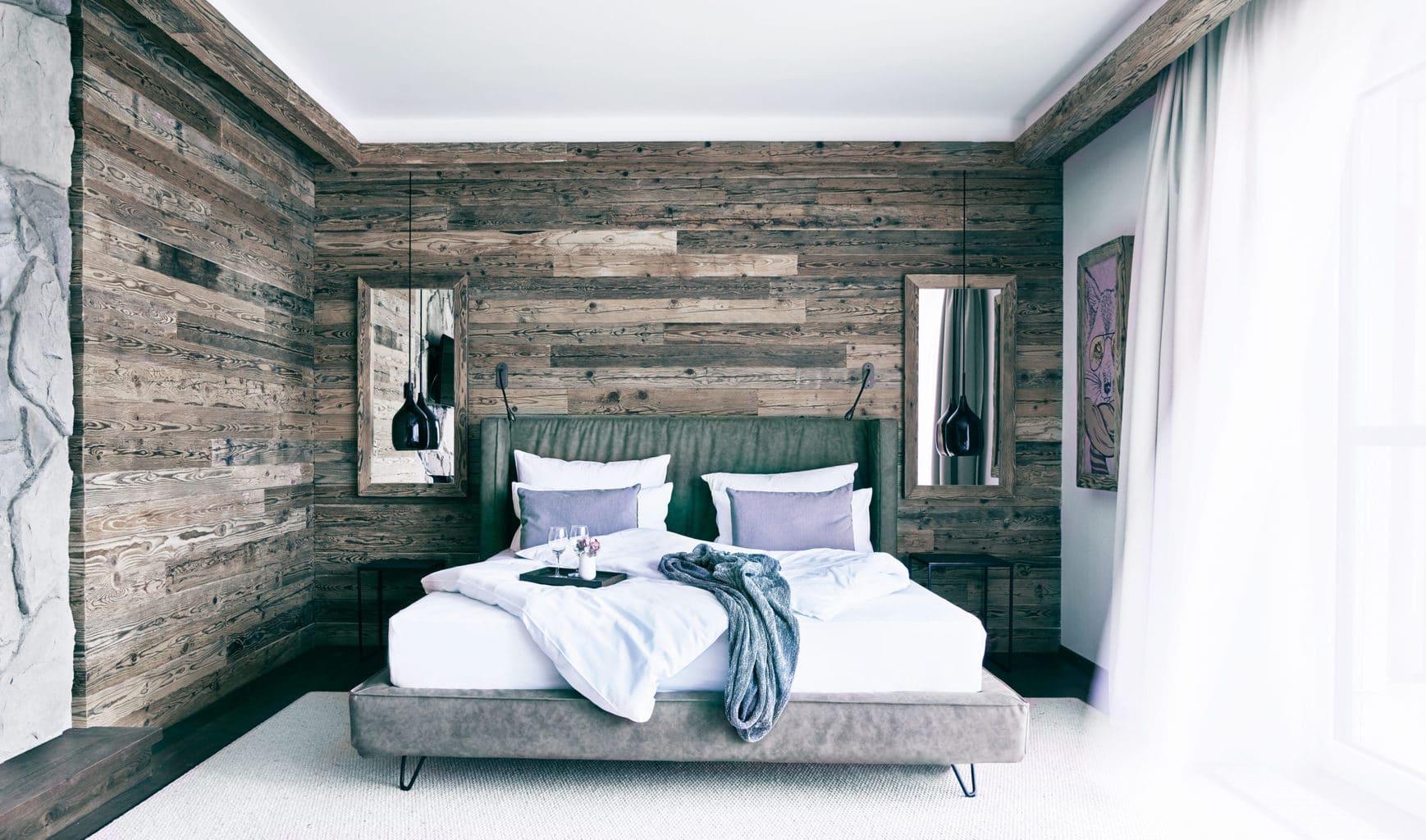 Tweepersoonskamer met houten bed in een suite van Landgut Voshövel aan de Nederrijn