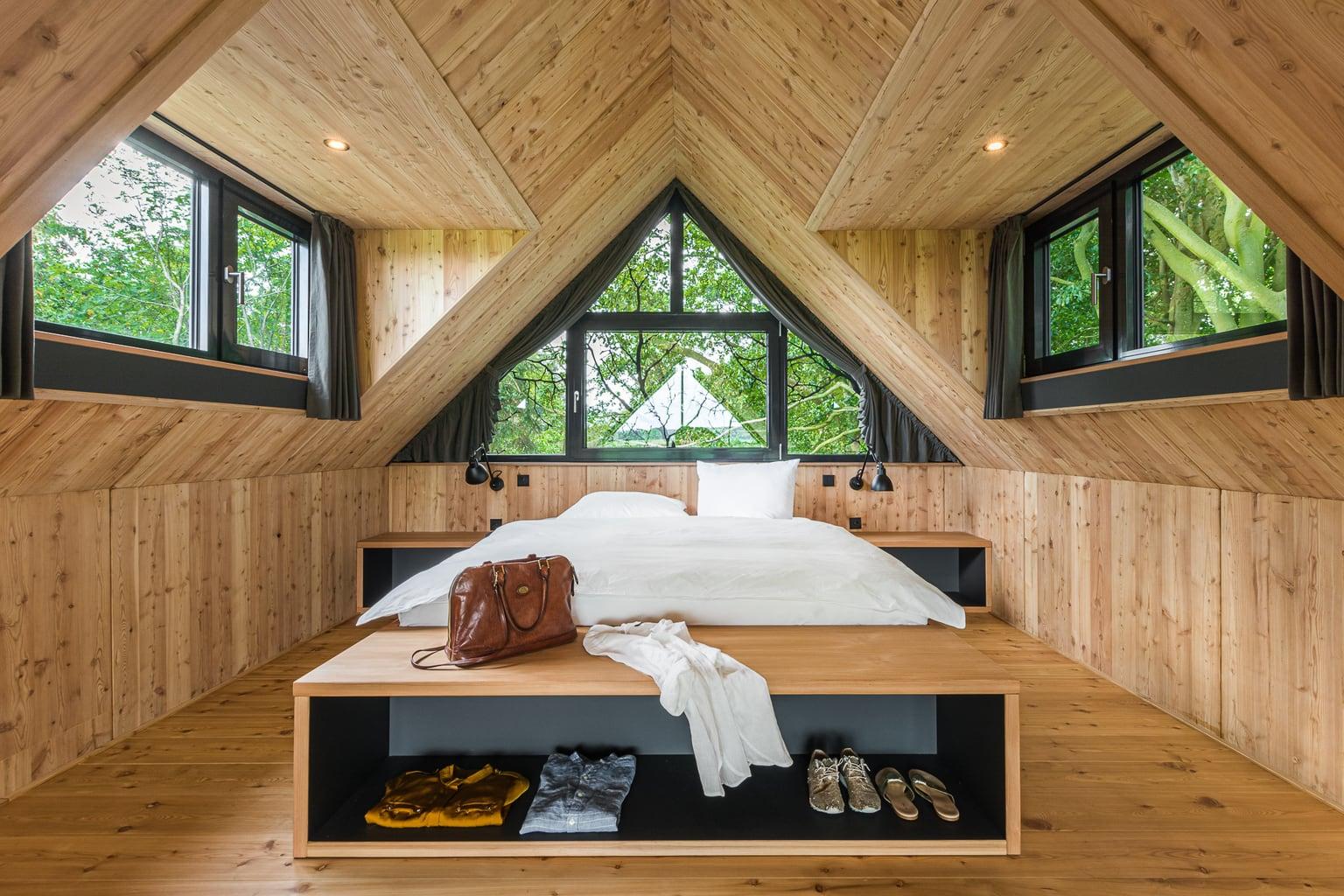 Slaapkamer in het boomhuis van Hotel Lütetsburg Lodges in Nedersaksen met veel hout