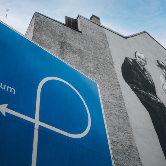 Graffiti met kunstenaar Joseph Beuys en een bord dat wijst naar de ingang van een museum in Mönchengladbach