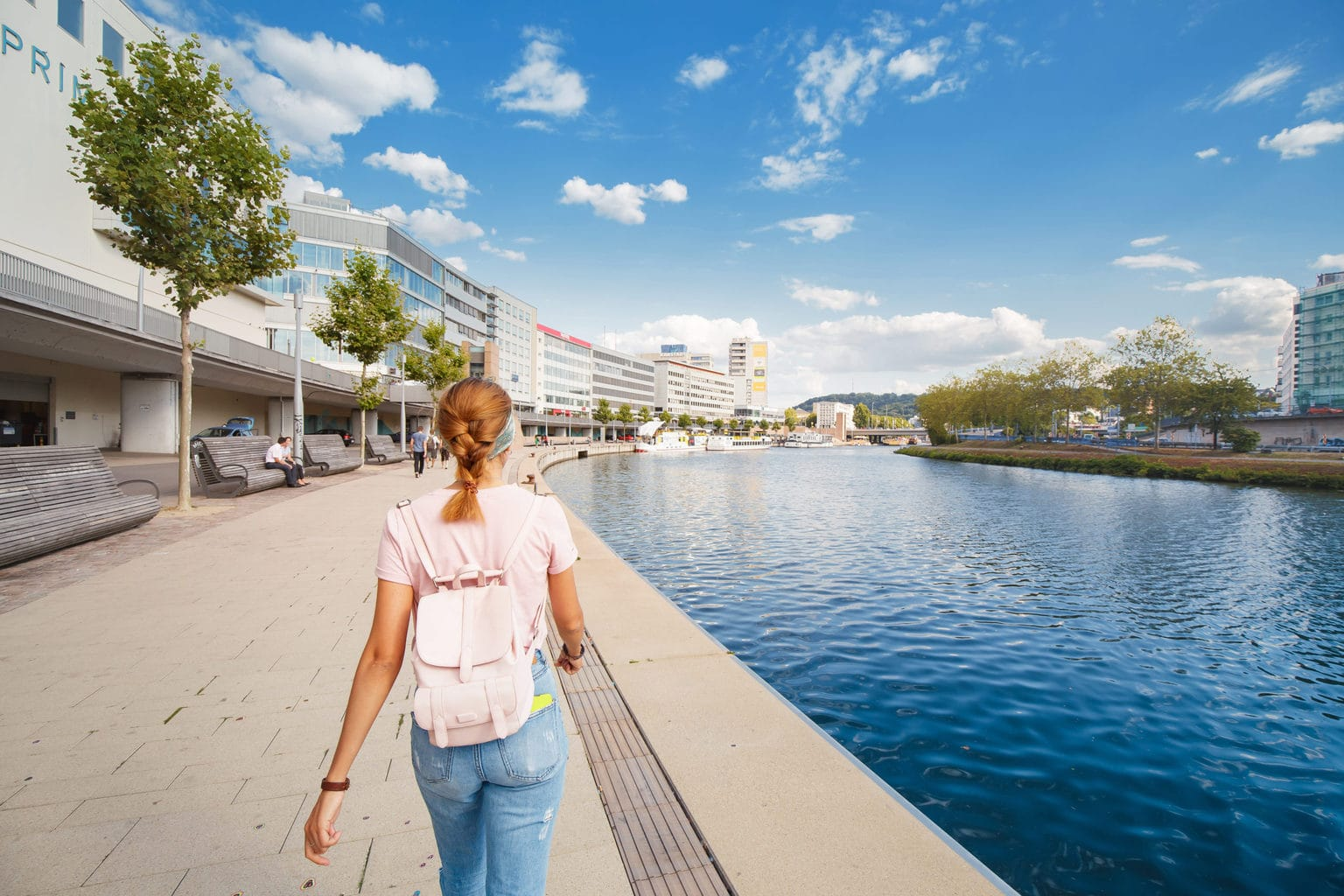 Een vrouw wandelt langs de oevers van de Saar in Saarbrücken