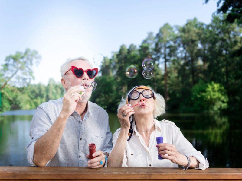 Een stel bestagers maakt zeepbubbels met een hartjesbril