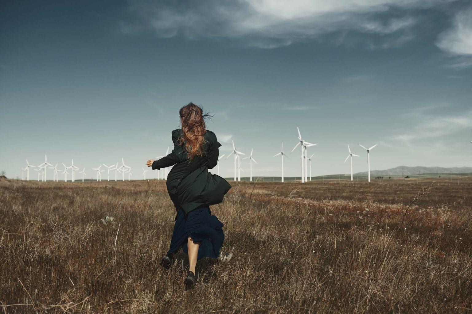 Vrouw loopt door een veld in richting van eindturbine als symbool voor duurzame mode uit Duitsland