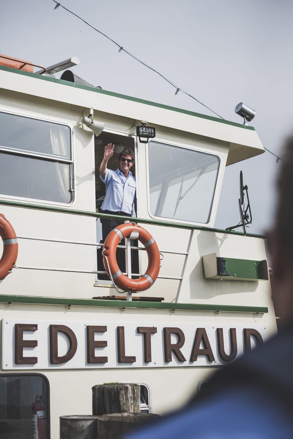 Kapitein Otto Strasser zwaait vanaf zijn boot Edeltraut op de Chiemsee