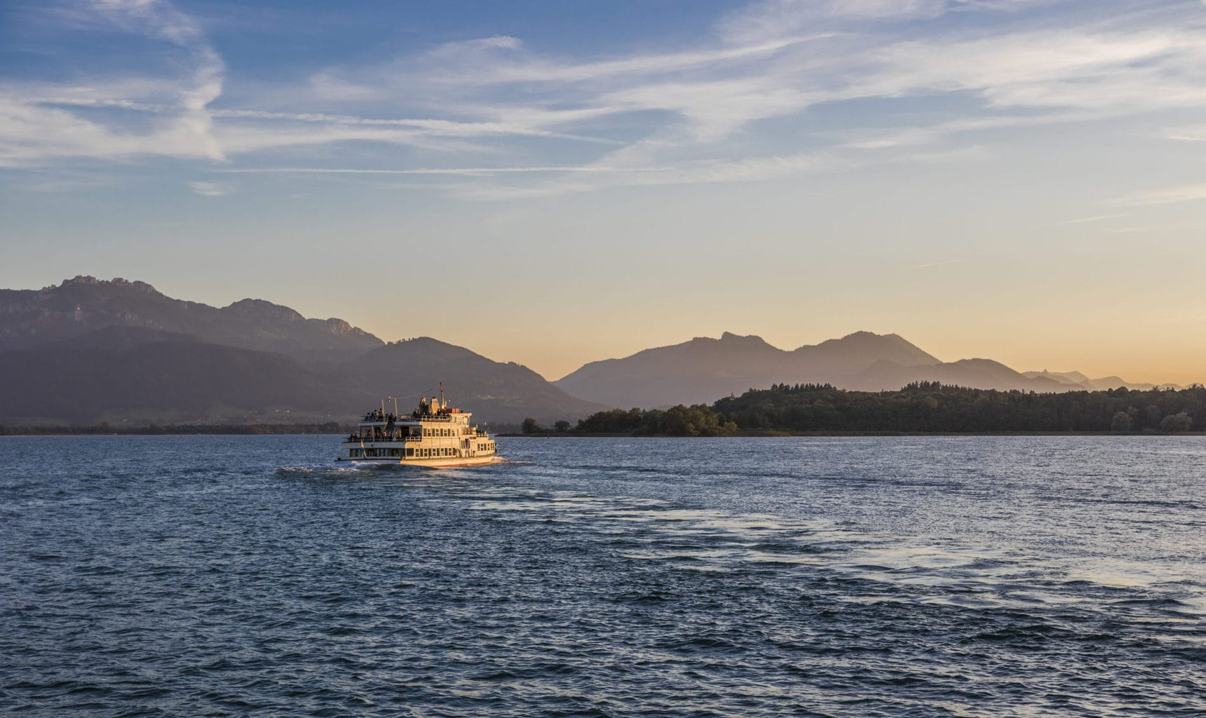 Een boot van de Chiemsee Schifffahrt op het meertje voor de bergen