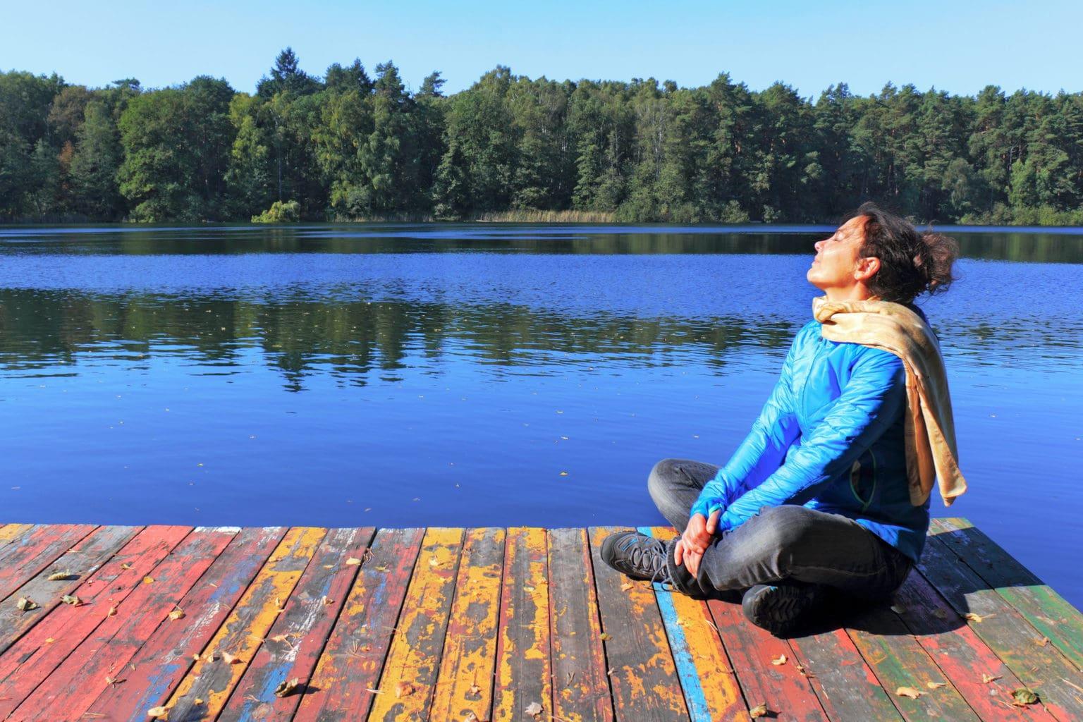 Een vrouw geniet van de zon aan een meer in Brandenburg