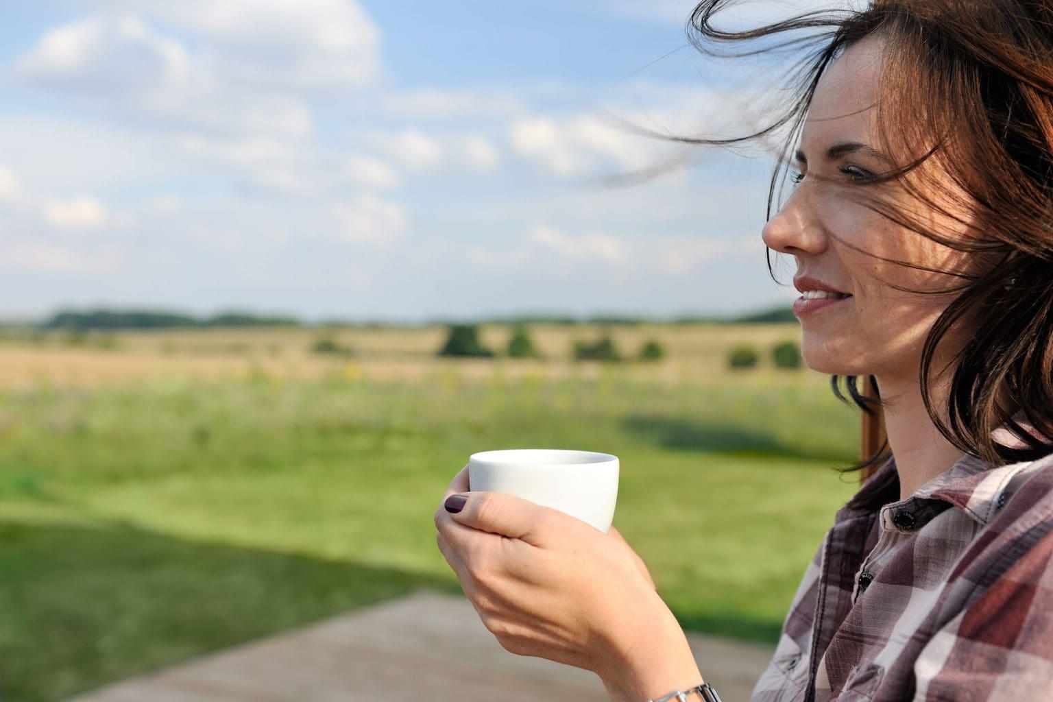 Vrouw geniet van een kop koffie met uitzicht op de natuur in de Hainichhöfe