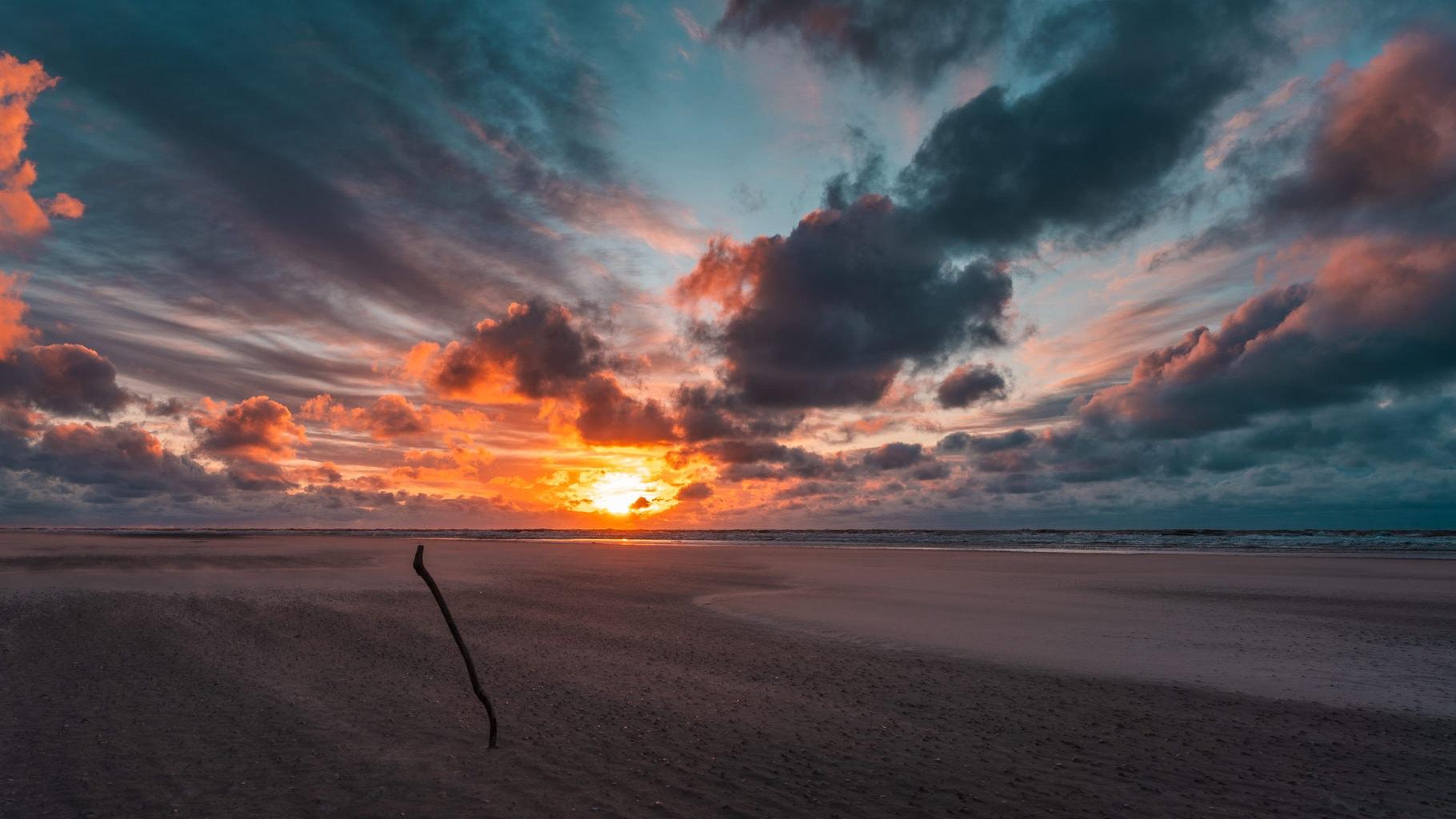 De zonsondergang boven het strand van noordzeeeiland is er een om van te genieten