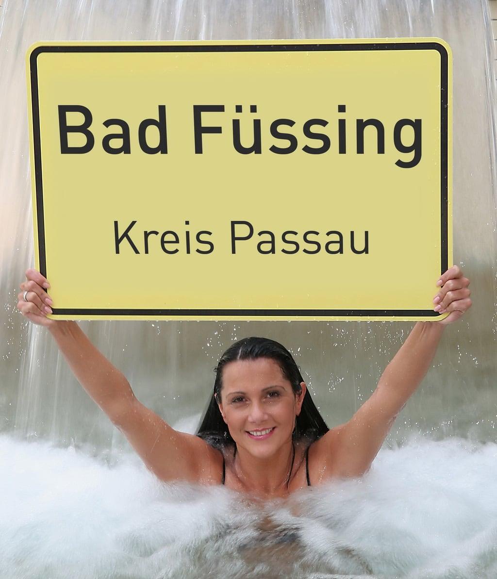 Een vrouw met een bord Bad Füssing in het water van de therme