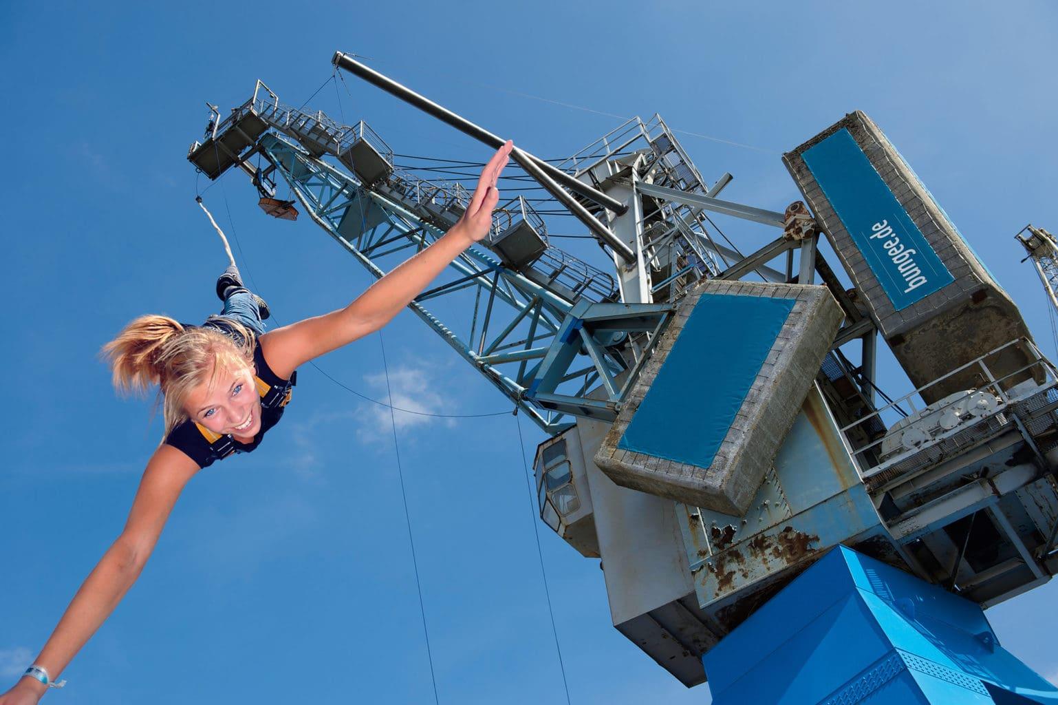 Een vrouw tijdens het bungee jumpen aan een havenkraan in Hamburg