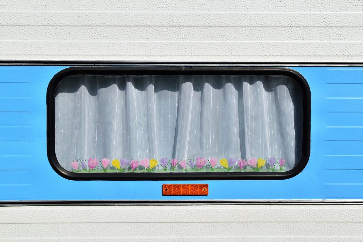 De ruit van een woonwagen of campervan met gesloten gordijn, de leukste Duitse camping aan het water