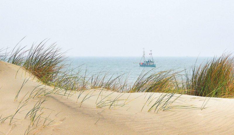 Een vissersboot achter de duinen van Spiekeroog
