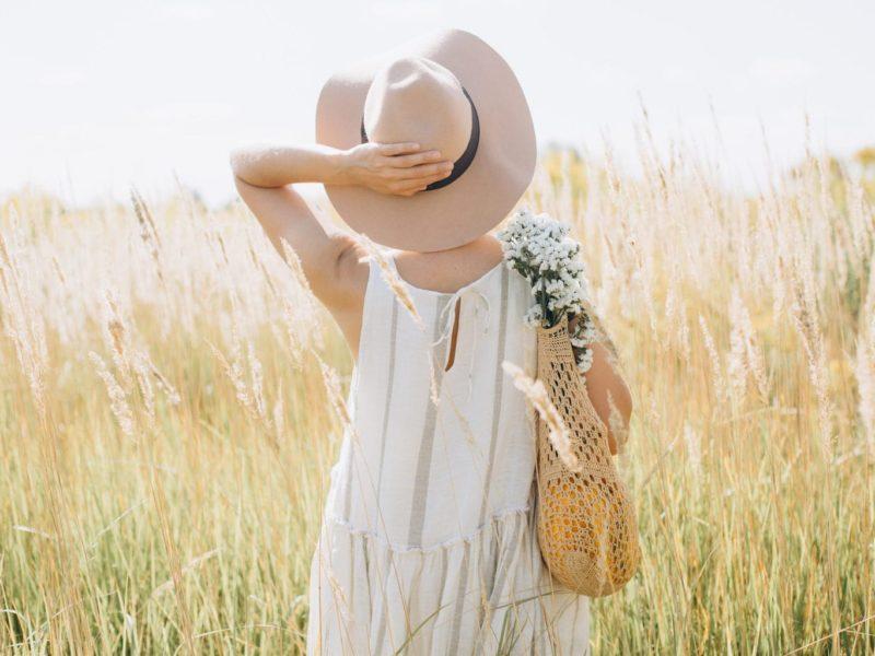 Vrouw met duurzame mode uit Duitsland staat in een granenveld