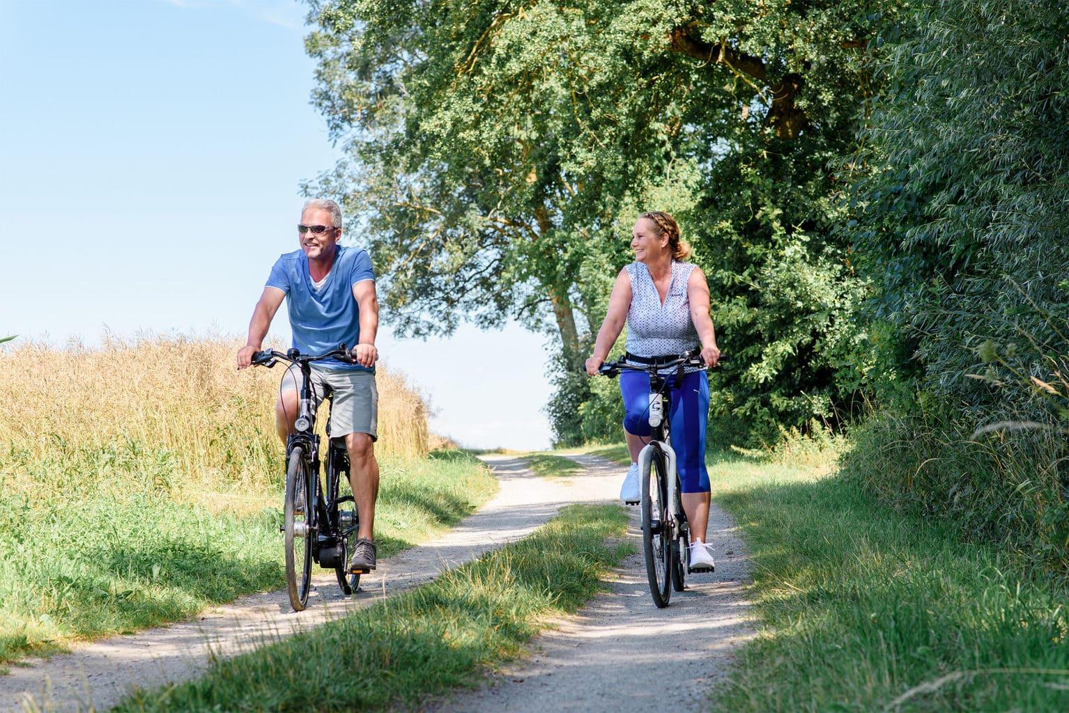 Man en vrouw fietsen met plezier op het platte land bei Bad Füssing