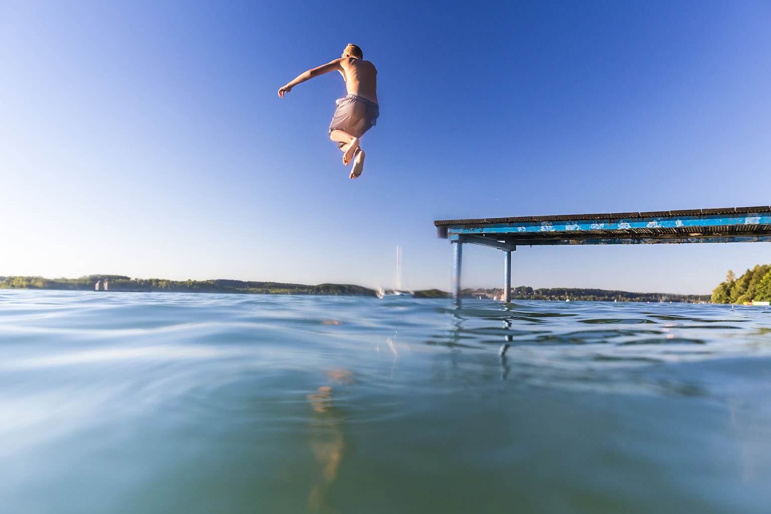 Jongen springt het water in