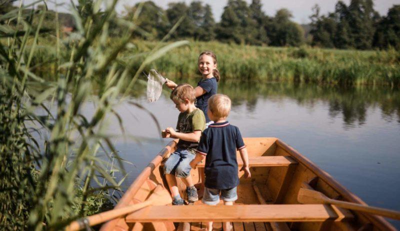 Kinderen spelen in een boot op het water bij een van de vakantieboerderijen in Beieren