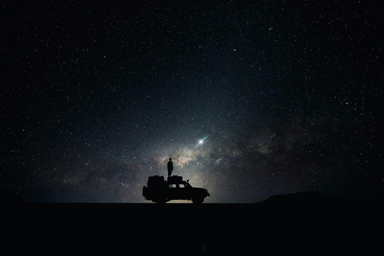 Een man staat op een camper onder de sterrenhemel in Hessen