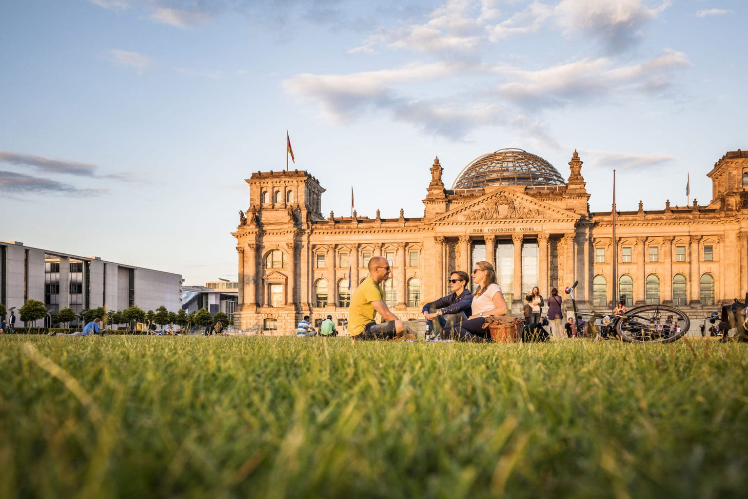 De Reichstag in Berlijn met jonge mensen op de voorgrond