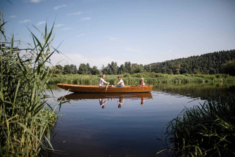 Een familie roeit in een boot in de buurt van vakantieboerderij Simmernhof in het Beierse Mossendorf