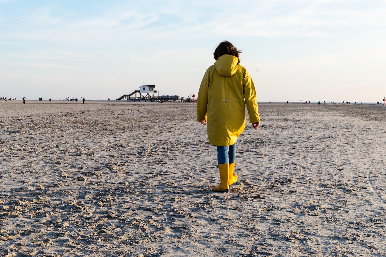 Vrouw in een regenjas op het strand van St. Peter Ording in Sleeswijk Holstein
