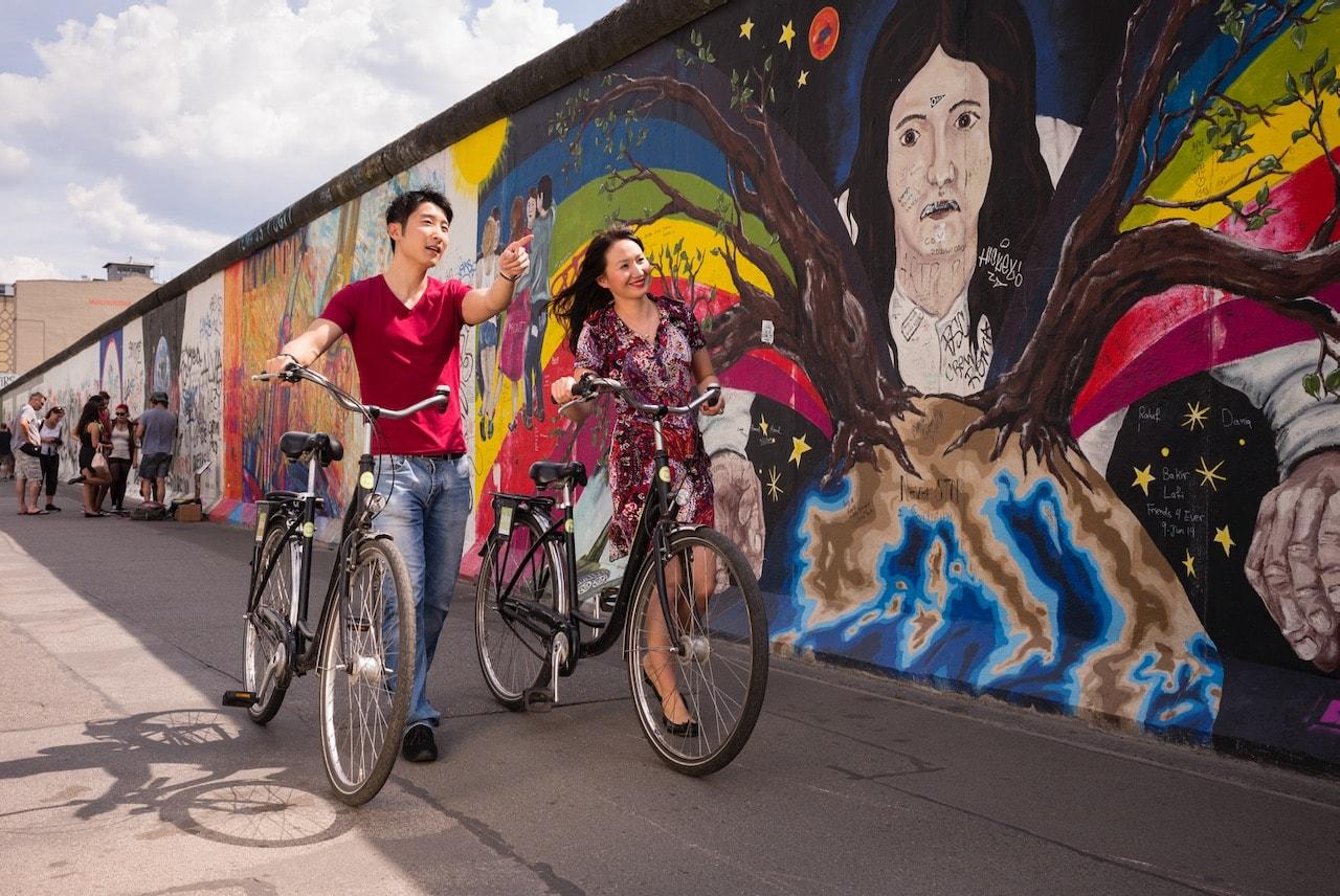 Asiatische bezoekers kijken nieuwsgierig naar de kunstwerken van de East Side Gallery