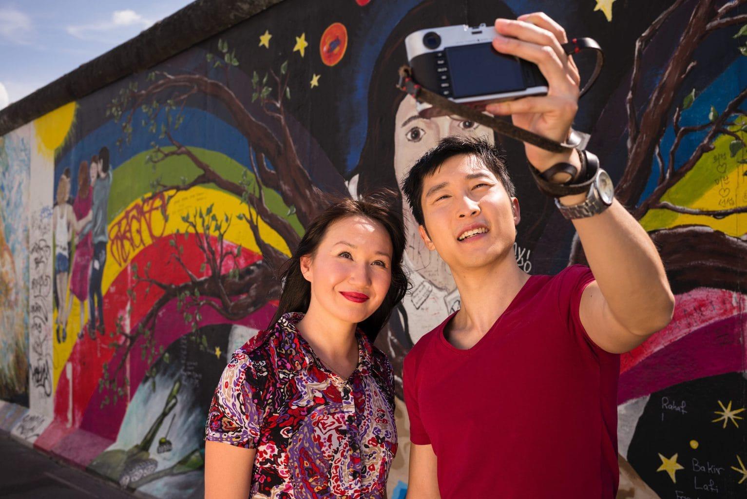 Asiatisch stel maakt een selfie voor de East Side Gallery in Berlijn