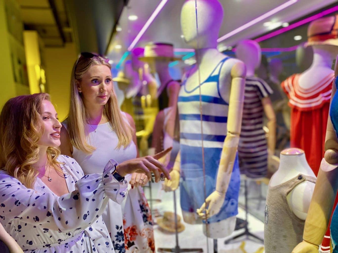 Zwei junge Damen blicken interessiert auf Exponate im BikiniArtMuseum wobei es sich um Bademode vergangener Zeiten handelt