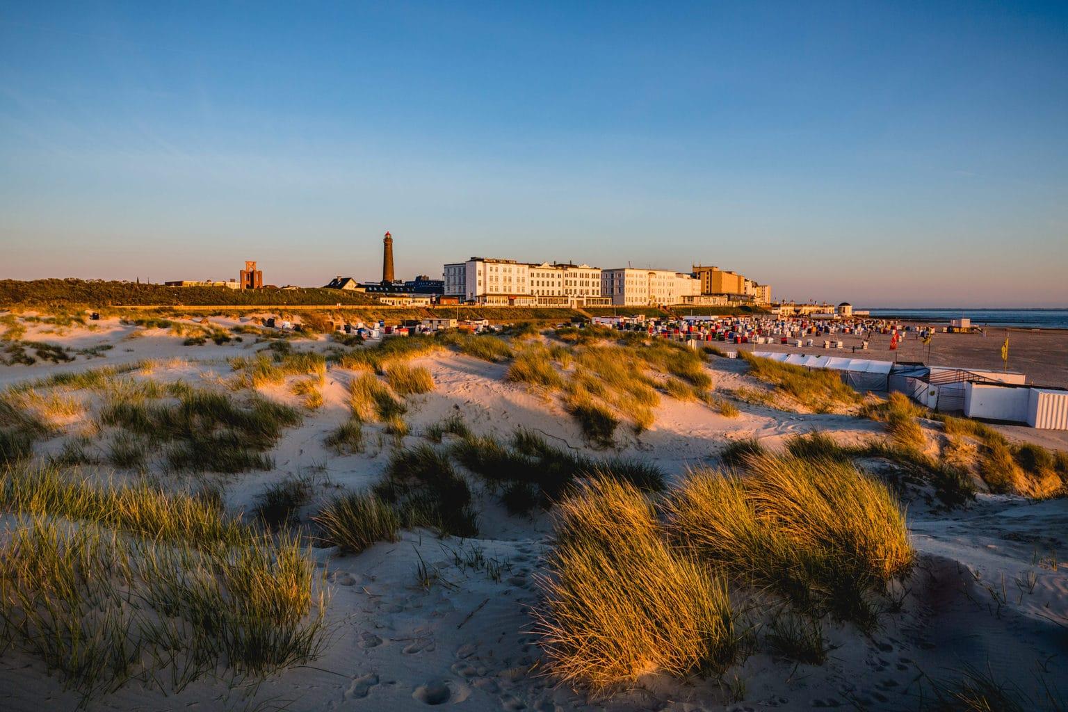 Duinen aan het strand van het Duits waddeneiland met vuurtoren en appartementen