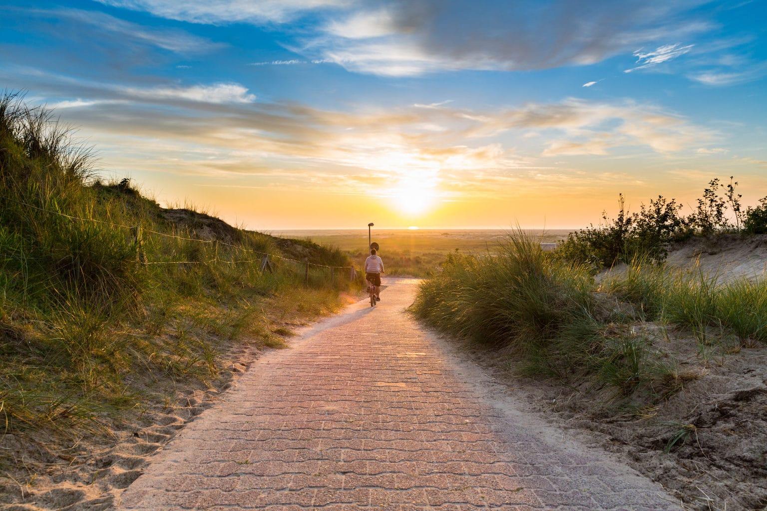 Fietser in de duinen op het eiland Borkum in Duitsland tijdens zonondergang