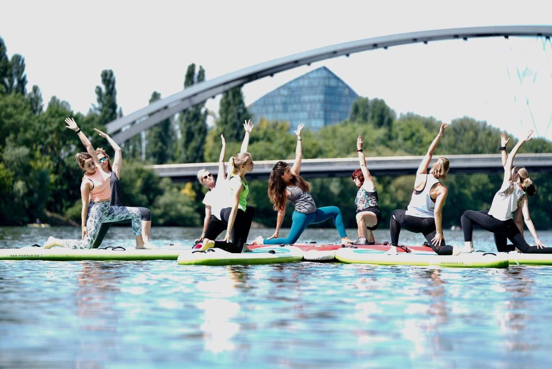 Suppers op hun Stand-up-Paddles zijn in Frankfurt bezig met yoga