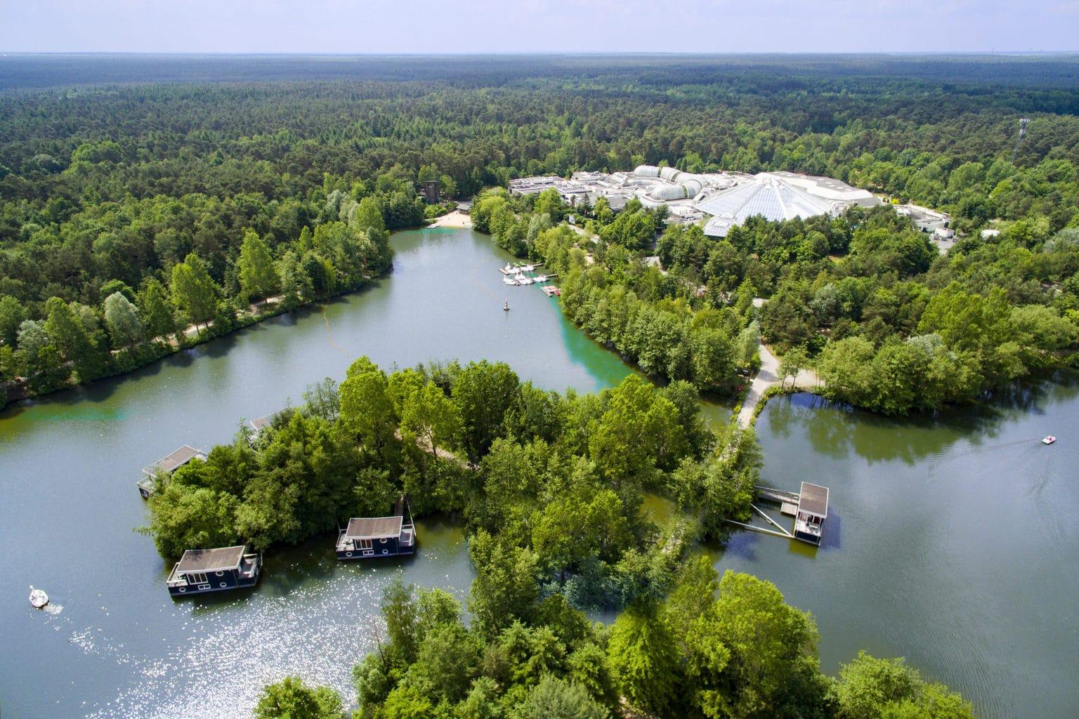 Luchtopname van Center Parks Bispinger Heide met drijvende vakantiehuizen op een meertje