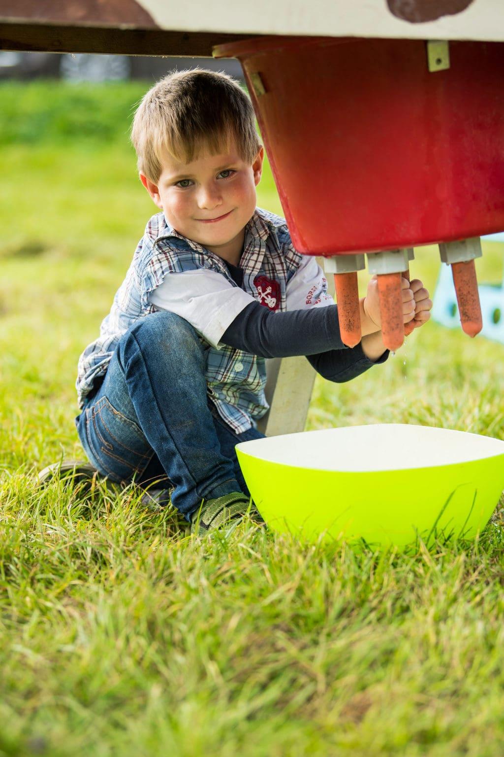 Een kleine jongen tap melk uit een houten koe