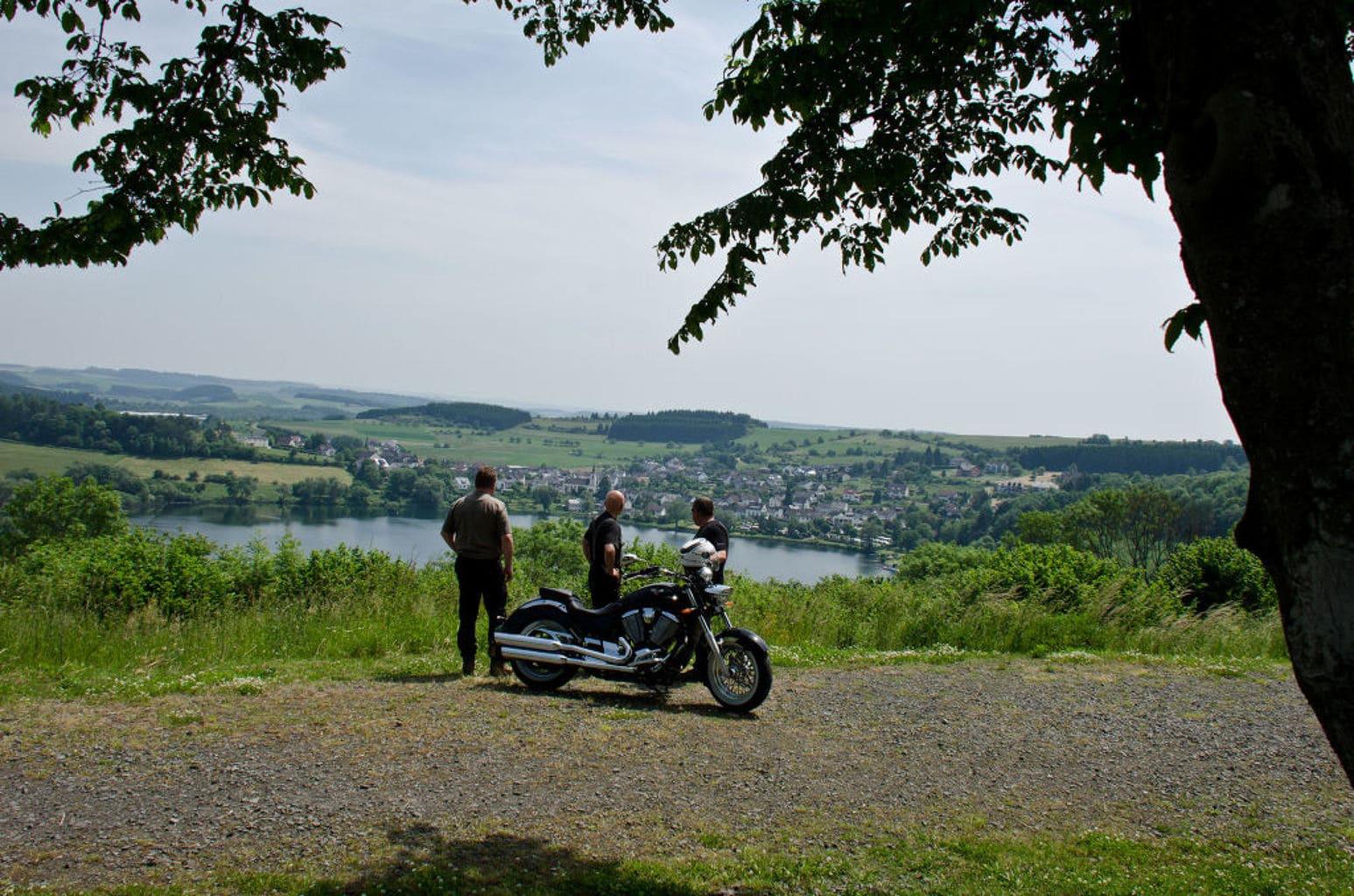 Motorrijders kijken op een vulkanisch meertje in de Eifel