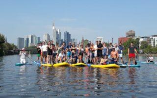 Stand-up-Paddle op de rivier Main voor de Skyline van Frankfurt