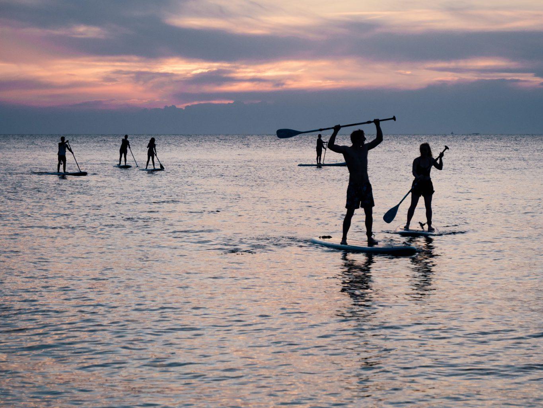 Stand-up-Paddlers of terwijl suppers in de zonsondergang op een meertje