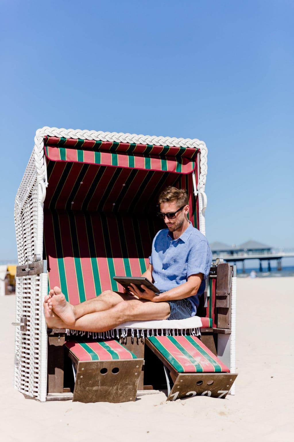 Een man zit in een strandkorf op Usedom