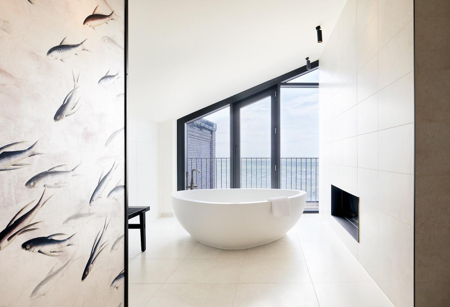 Verlichte badkamer met een vrij staande badkuip in Lighthouse Hotel te Büsum