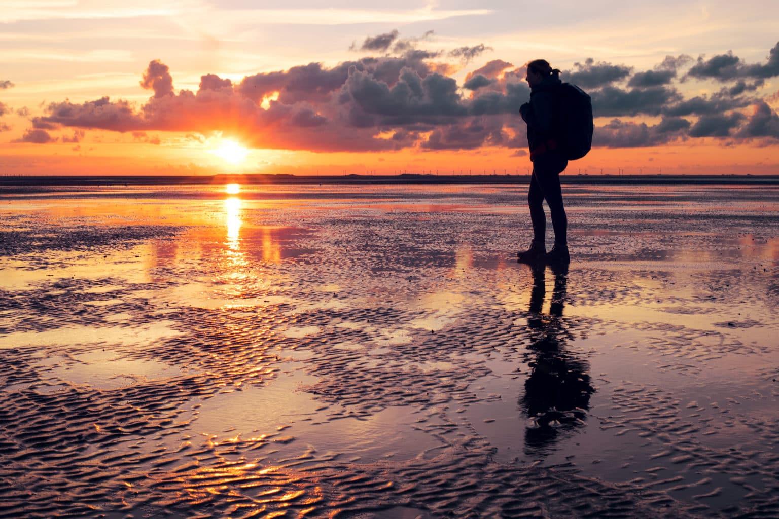Wandelaar op het was op het Duits eiland Borkum tijdens zonsondergang