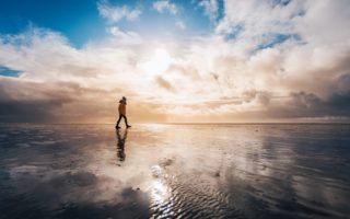 Een eenzame wandelaar op het wad bij het eiland Borkum in Duitsland