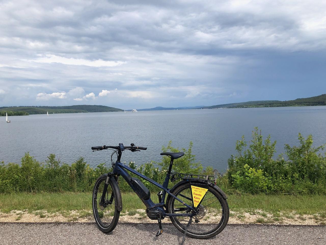 Een e-bike staat op het dam dat door het mideen van de Grosse Brombachsee in het Frankse merengebied loopt