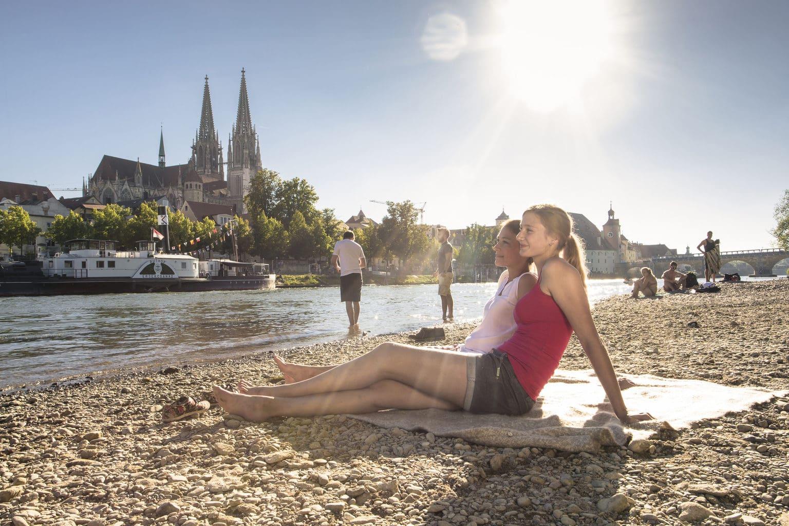 Twee dames vermaken zich aan de Donaubank in Regensburg