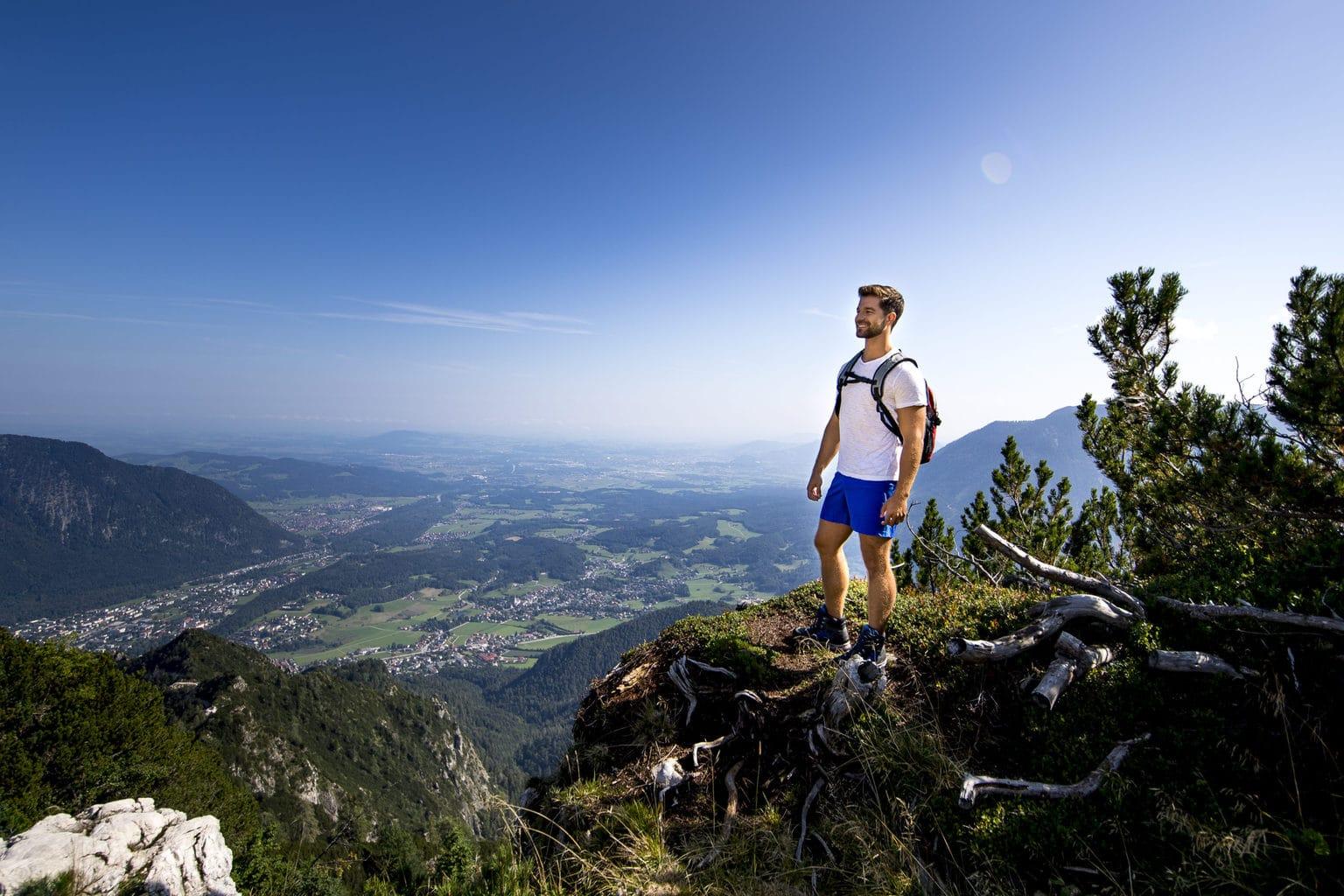 Een man lacht over beide bekken na de beklimming van een berg in het Berchtesgadener Land