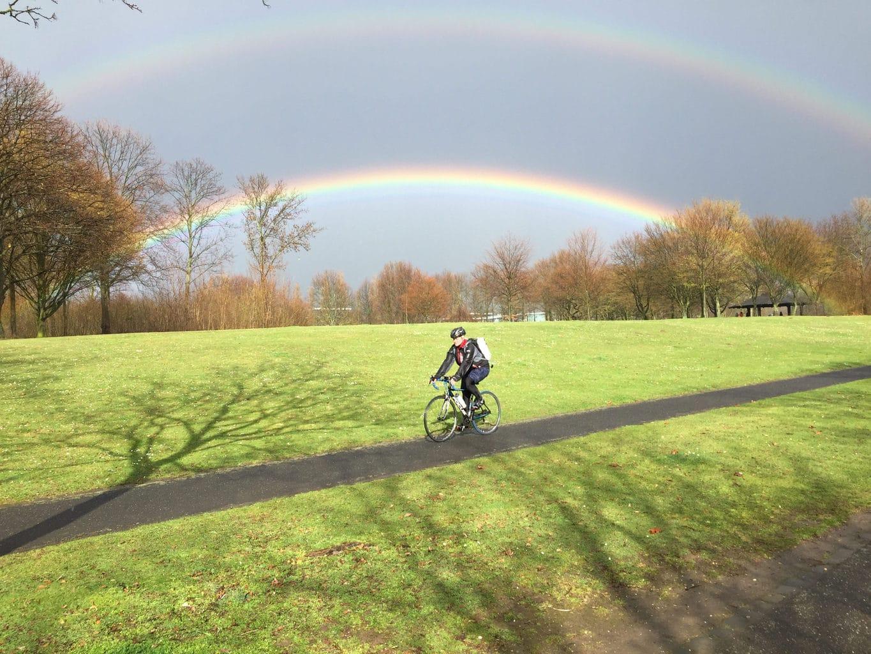 Fietser onder een regenboog in de Rheinaue in Bonn