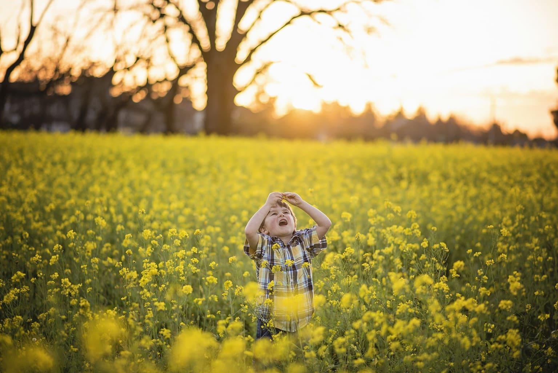 Een jonge speelt in een mosterveld met veel gele bloemen in Oostduitsland